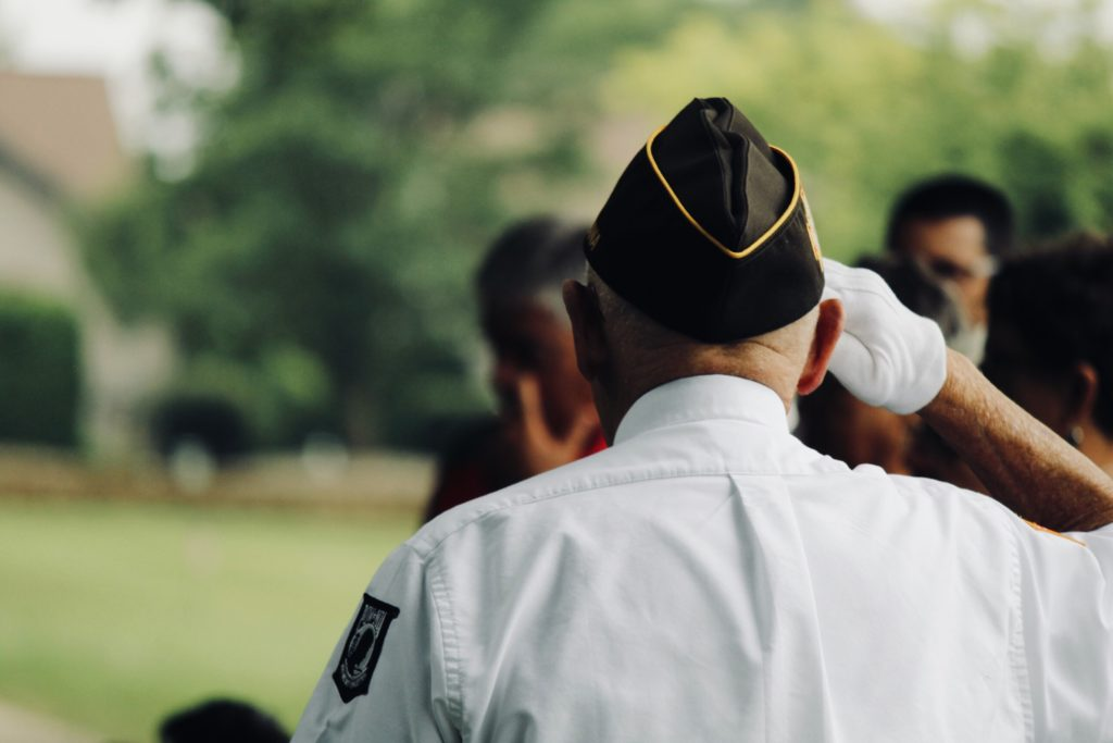 A man in a military uniform, saluting, with his back to the camera,.