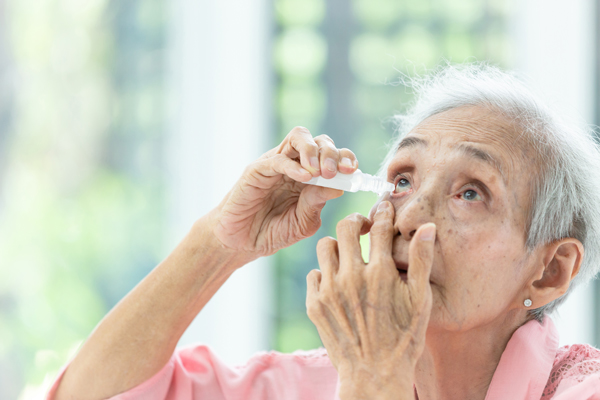 Older woman applying eye drops