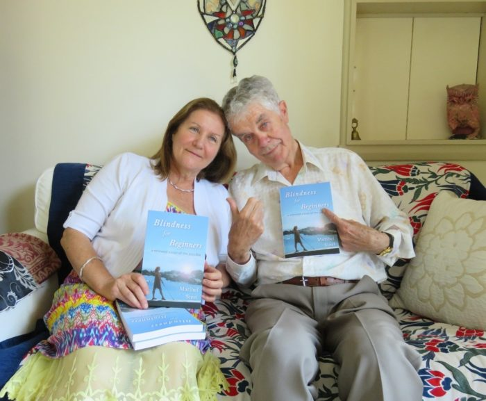Maribel and her father sitting together, her father proudly holding up a copy of her book