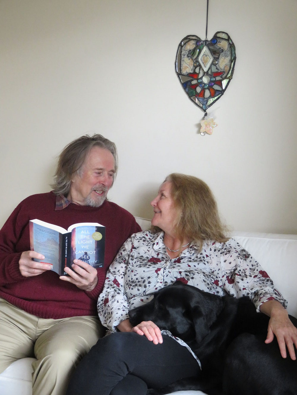 man reading book to woman and her guide dog