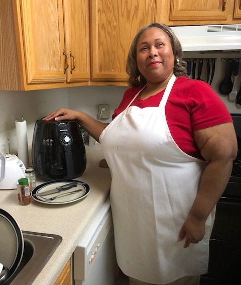 woman standing in kitchen with hand on top of air fryer