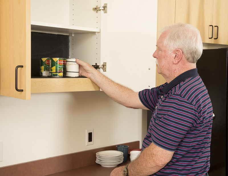 Man inventorying food in cabinet. Cans are labeled with large print labels