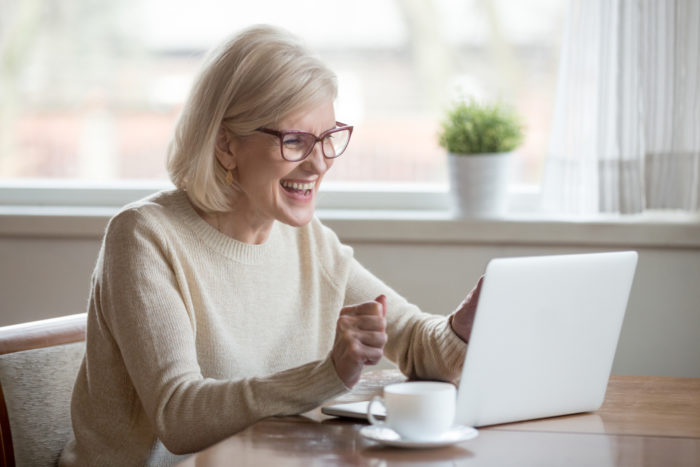 Senior woman smiling looking at laptop as if talking to someone