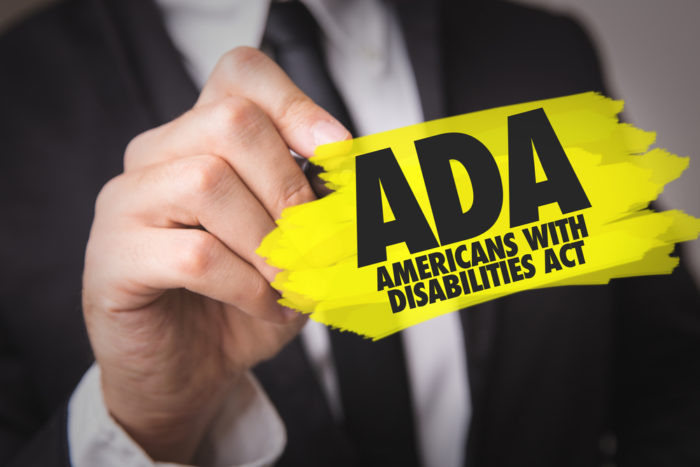 Man in suit holding small sign that says ADA Americans With Disabilities Act