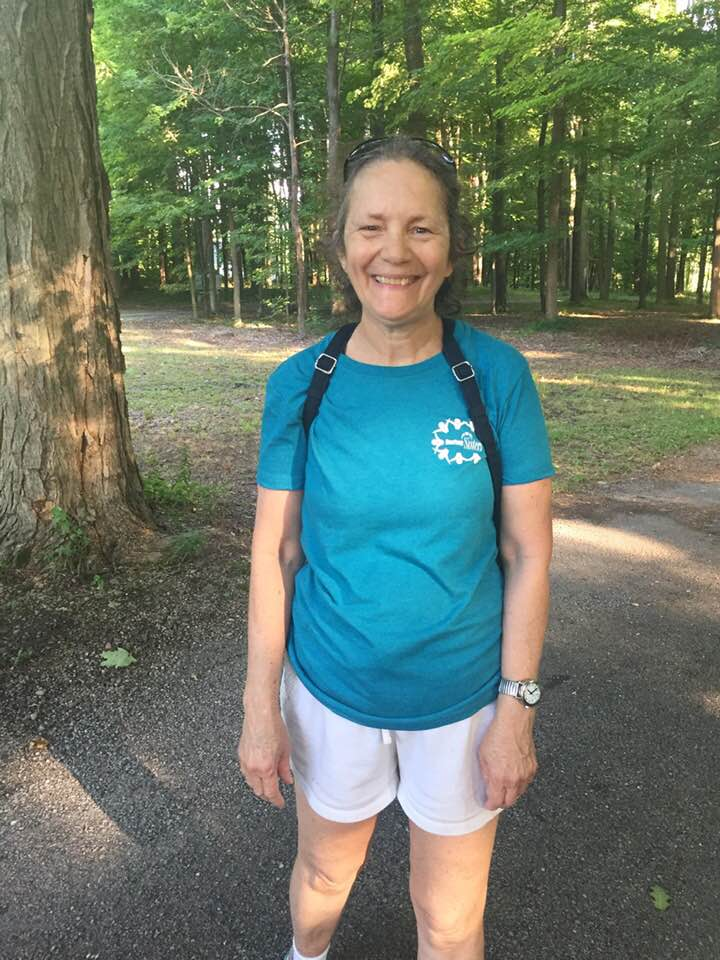 """Amy smiling and standing on path in park wearing her """"Daring Sisters"""" turquoise t-shirt"""