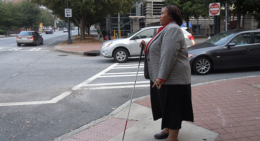 woman with white cane extended getting ready to cross the street
