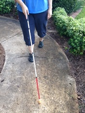 person walking on sidewalk using white mobility cane