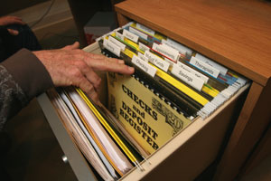 File drawer with large print labels and hand of person going through the drawer