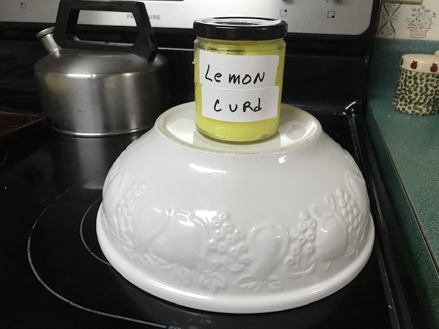 Jar of lemon curd displayed on stove top