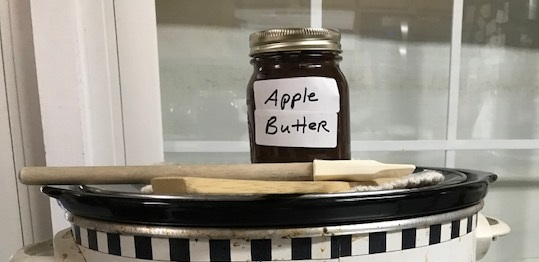 Jar of homemade apple butter sitting on top of crock pot