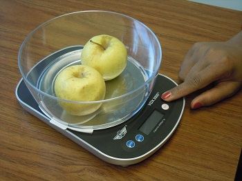 talking food scale with bowl of yellow apples on it. finger points to the controls