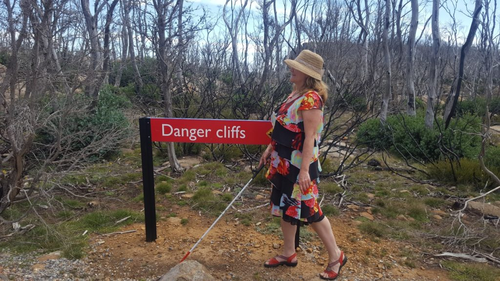 "maribel standing on cliff next to sign ""Danger cliffs"". She is wearing a hat and holding out her white cane. photo by Harry Williamson"