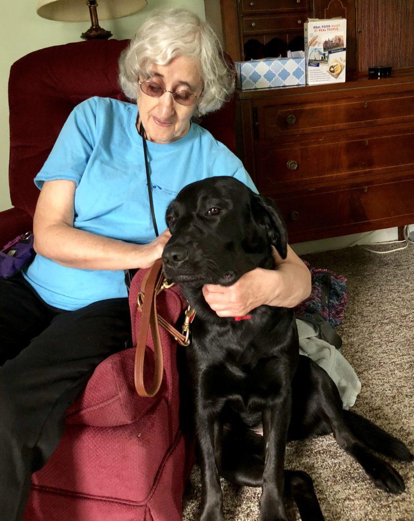 Sandra sitting with arms around black dog guide