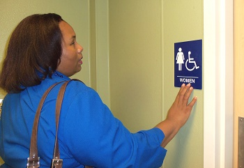 woman reading braille on women's bathroom sign