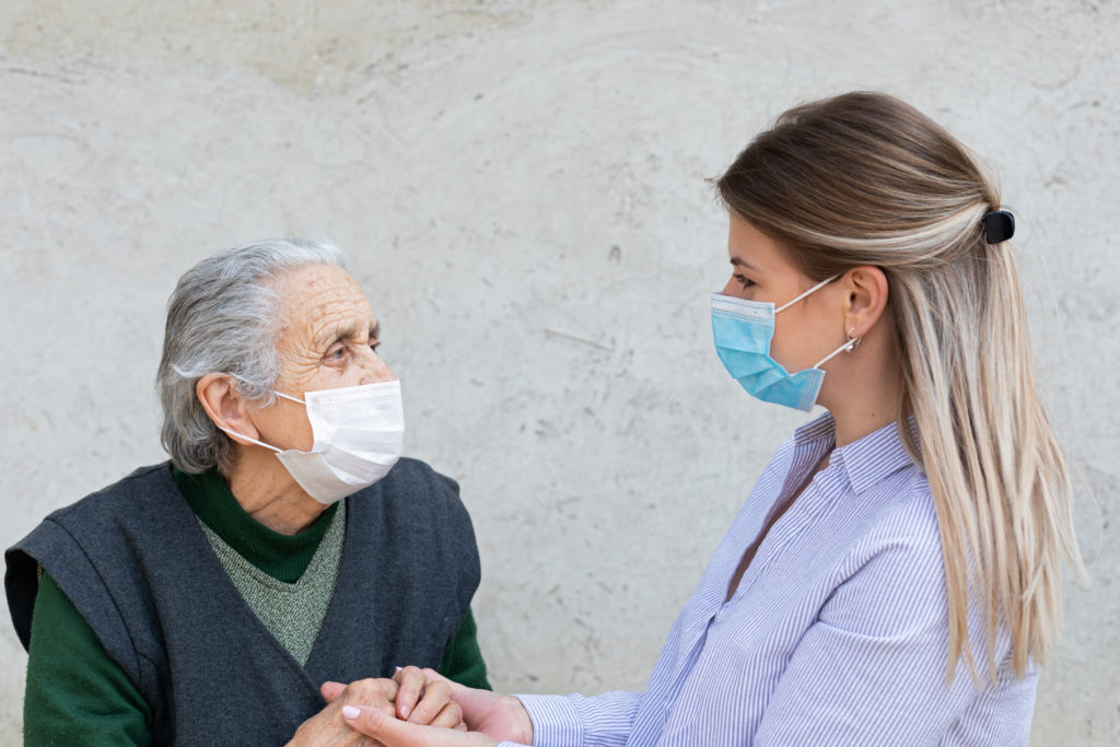 Two people, one senior and one younger are talking while wearing masks.