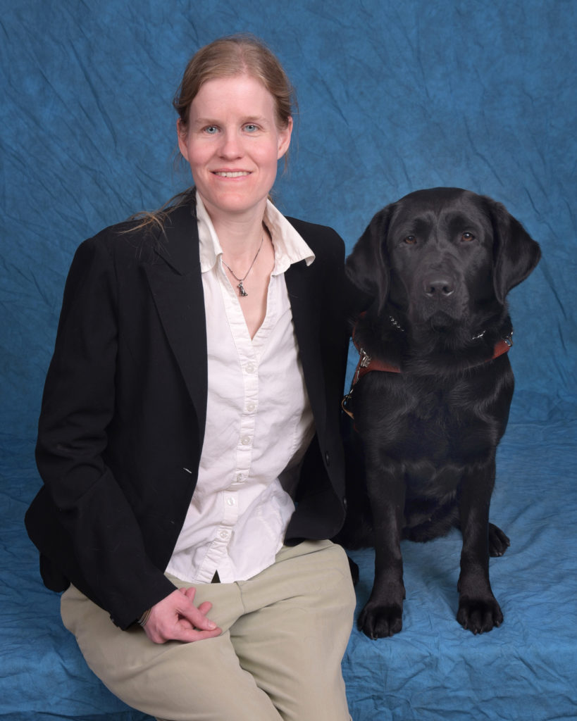 Elizabeth sitting with her black lab dog guide Ocala