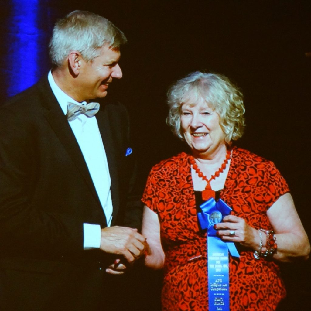 Lynda with Craig Meador at APH winning award for artwork. She is holding a blue ribbon and wearing a red dress and red necklace.