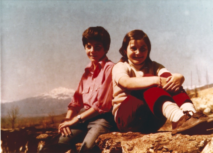 Maribel and brother as children seated next to each other on mountaintop with snow covered mountain in background