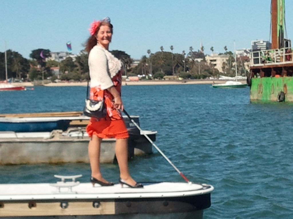 Maribel Standing on Pier with white cane in front of her (Photo by Harry Williamson)