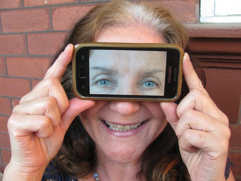 Maribel holding magnifier to her eyes. Photo by Harry Williamson
