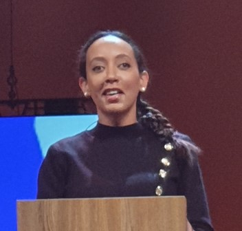 Haben Girma at a podium speaking. photo by Lexane Sirac This file is licensed under the Creative Commons Attribution 4.0 International license.