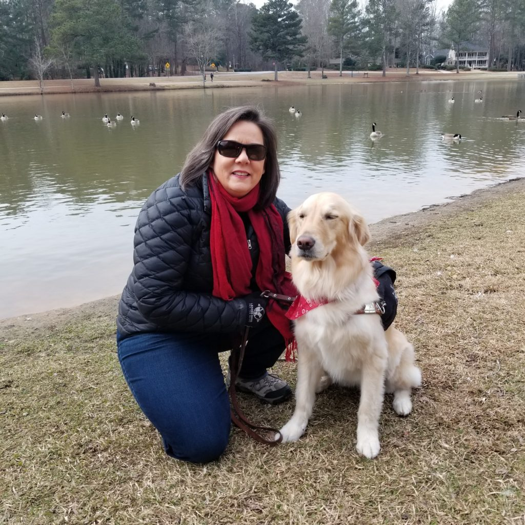 Audrey kneeling by guide dog in front of lake with geese swimming