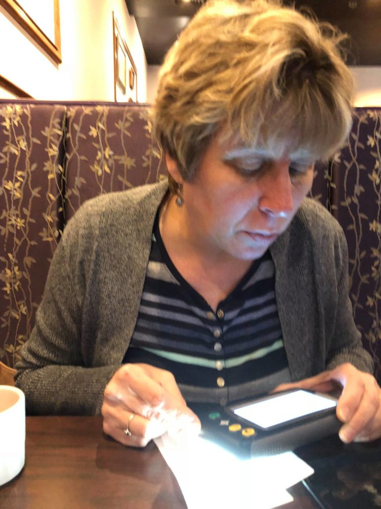 Beckie reading menu at restaurant with hand held video magnifier
