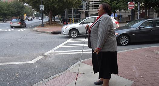 Empish using white cane to cross street