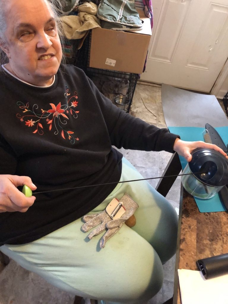 Jeannie using pull chopper. Butcher's glove and palm peeler are on her lap.