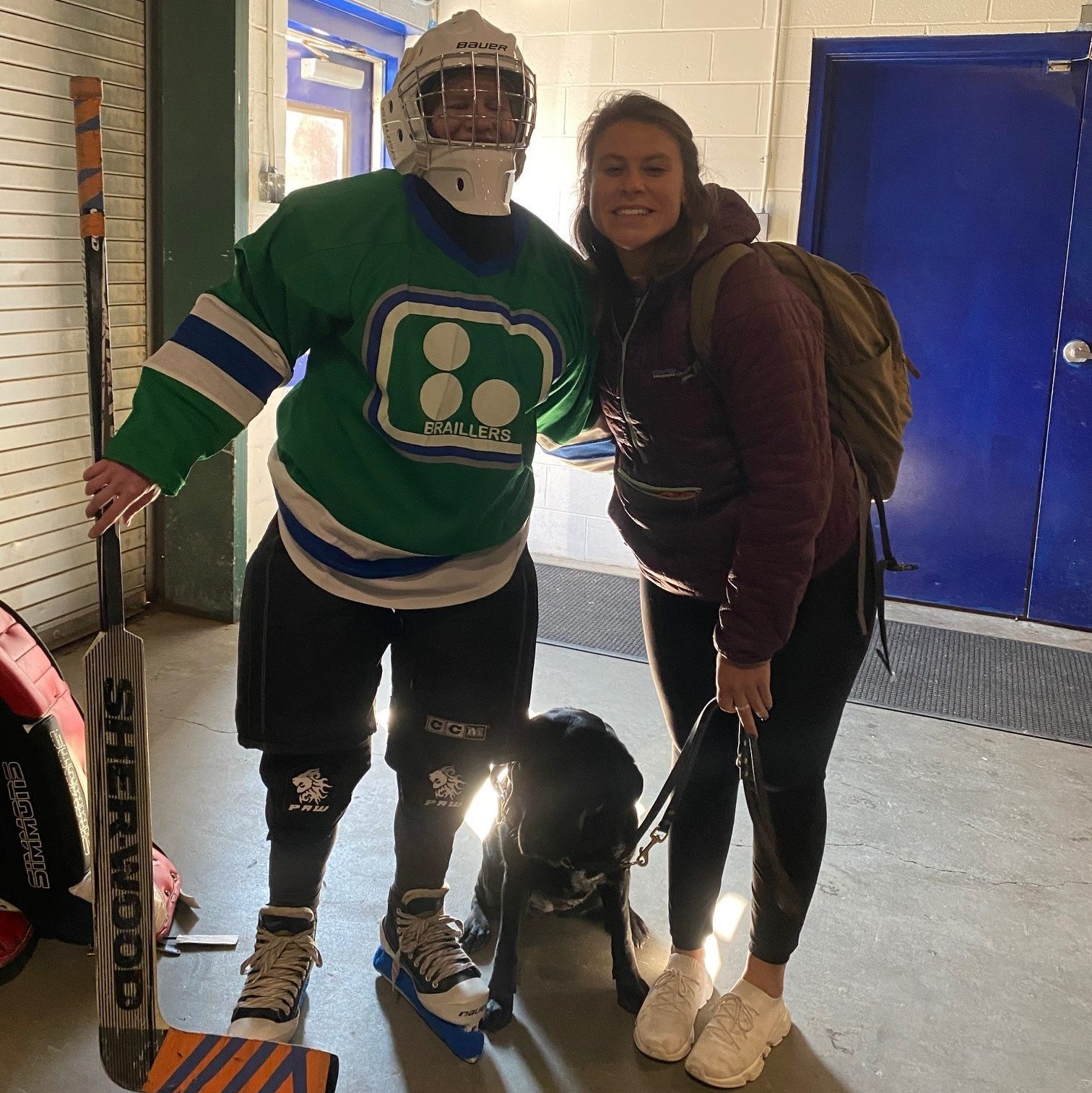 Liz Bottner dressed in hockey gear, her guide dog Guiding Eyes Ocala, and  Ocala's puppy raiser Samantha Epstein