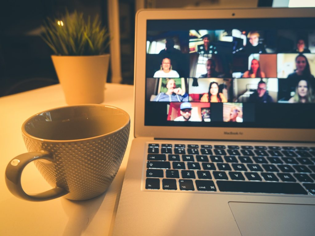 laptop computer with zoom group showing on screen and coffee cup sitting next to computer.Photo by Compare Fibre on Unsplash