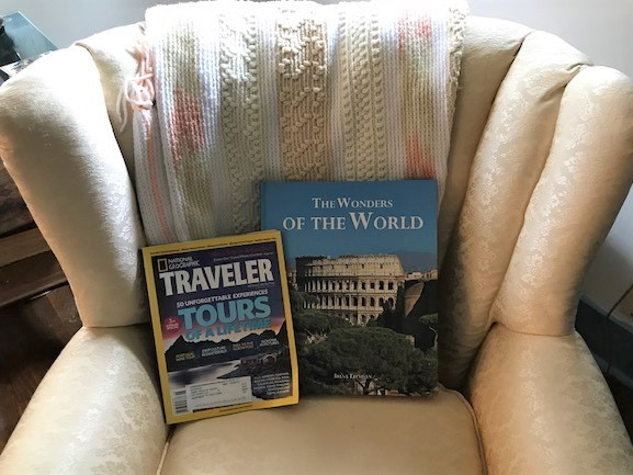 armchair with two travel books: The Wonders of the World and National Geographic Traveler Tours