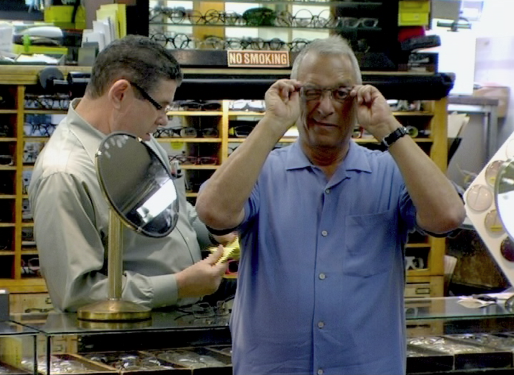 Joe in optical shop trying on Glasses