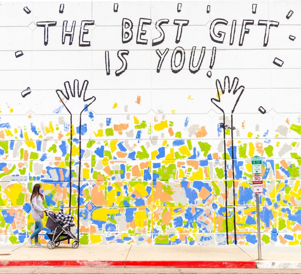 """picture of mural on wall with two hands pointing to words """"The Best Gift is You!"""" in the lower foreground is a woman with a stroller walking by. Photo by Dakota Corbin on Unsplash"""