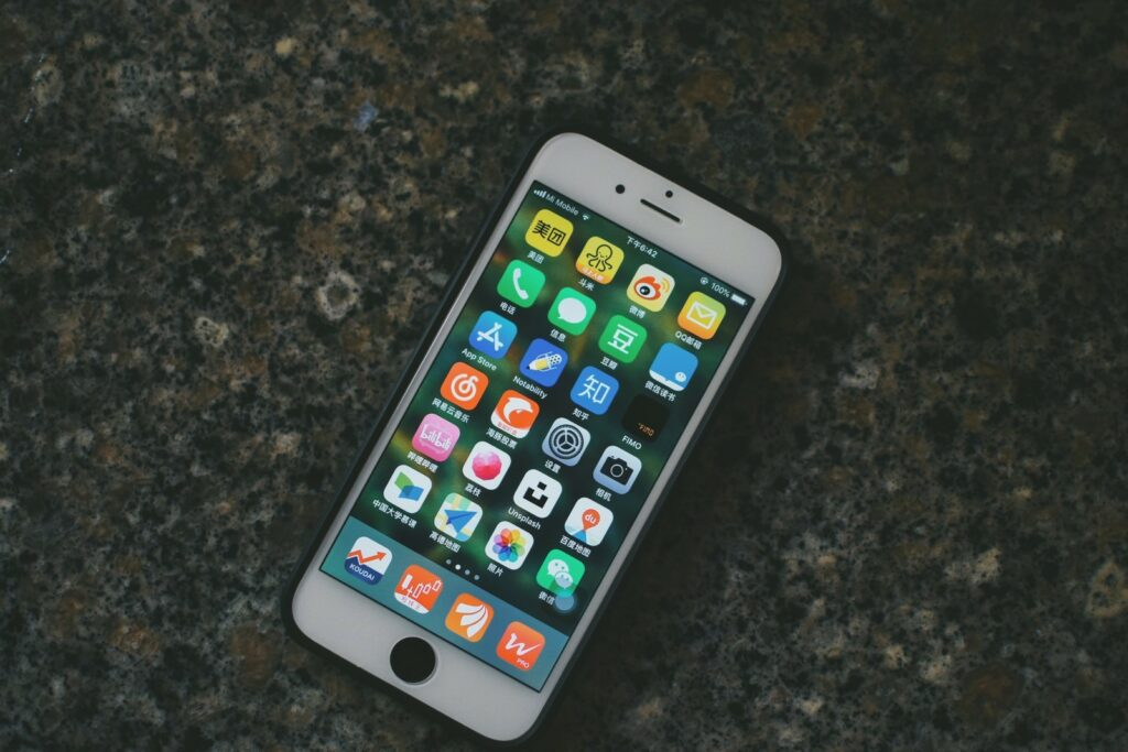 iPhone home screen with apps. Photo by Jizhidexiaohailang on Unsplash