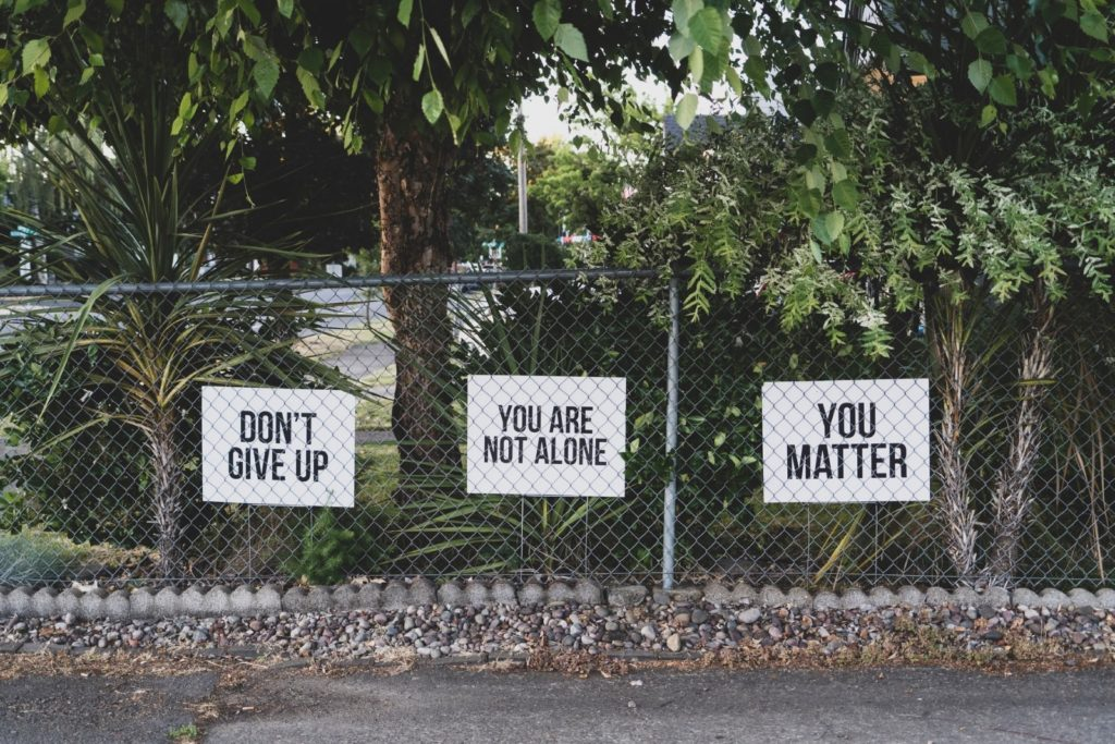 """signs on fence saying: """"Don't give up"""" """"You are not alone"""" """"you matter"""""""