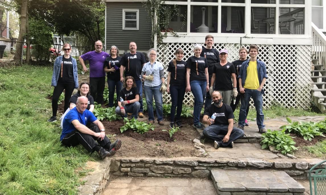 volunteers planting garden in front of house