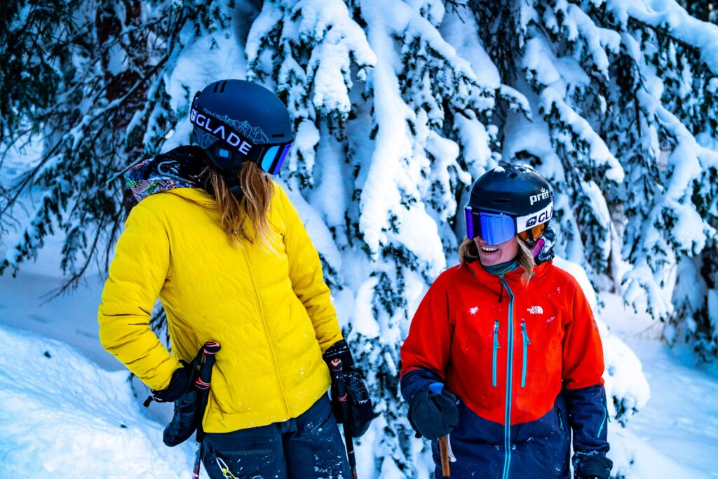 Two people in brightly colored ski gear in a snowy background