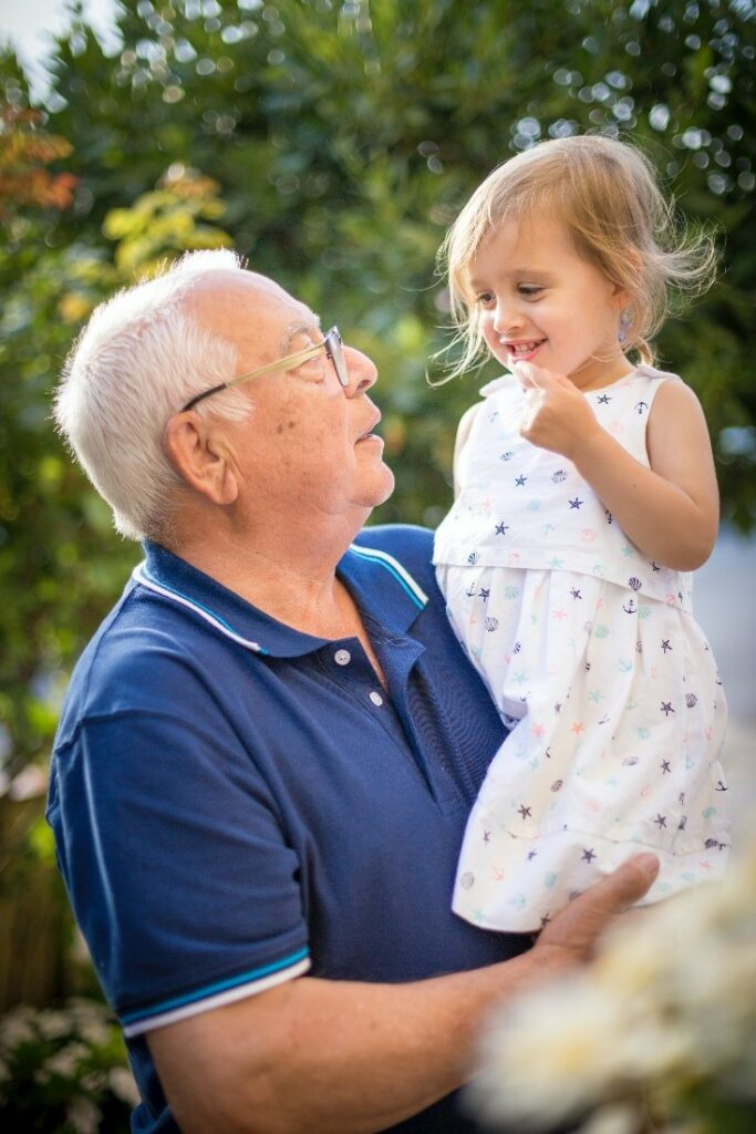 grandfather holding small child Photo by Isaac Quesada on Unsplash