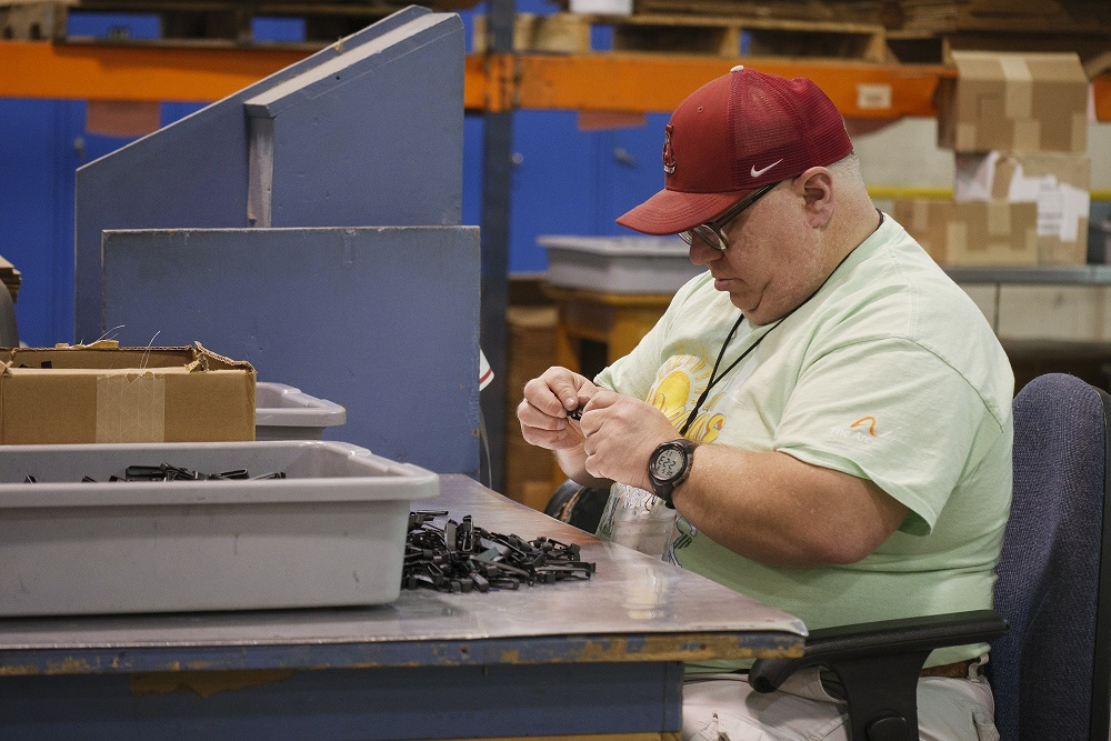 Man sitting at work bench sorting parts