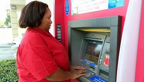 VisionAware Peer Advisor, Empish Thomas, using an ATM independently.