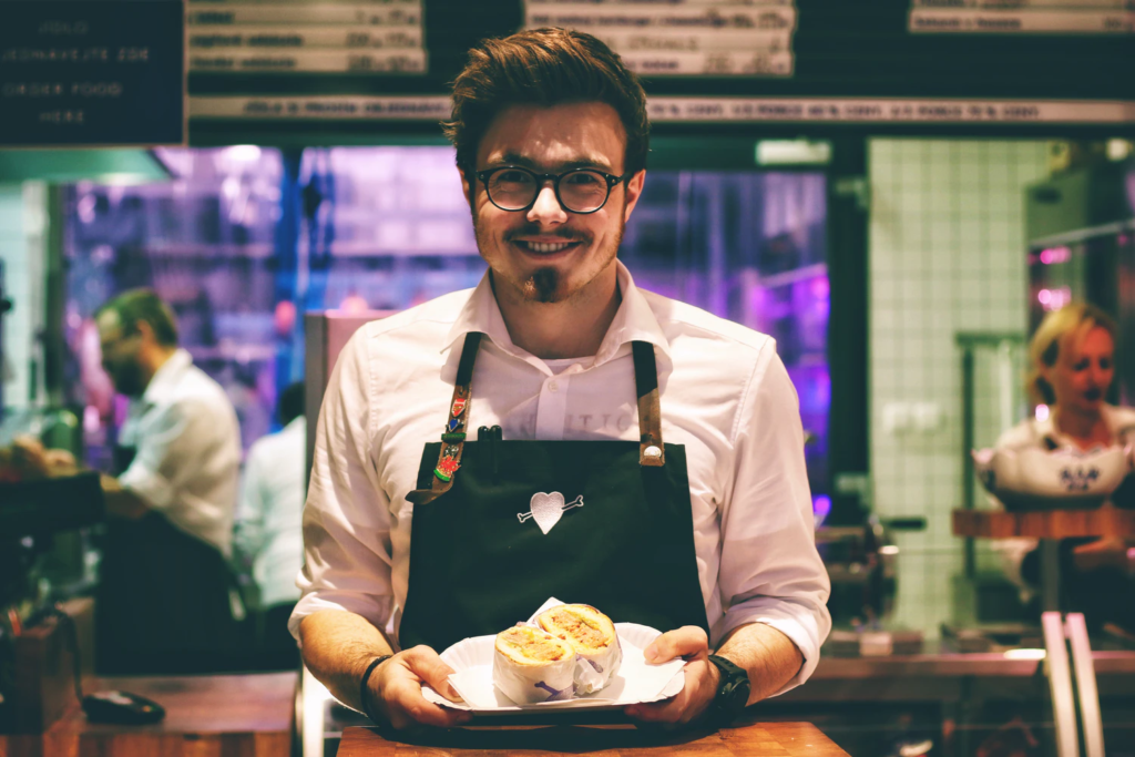 Photo of a man wearing an apron holding a plate of food.