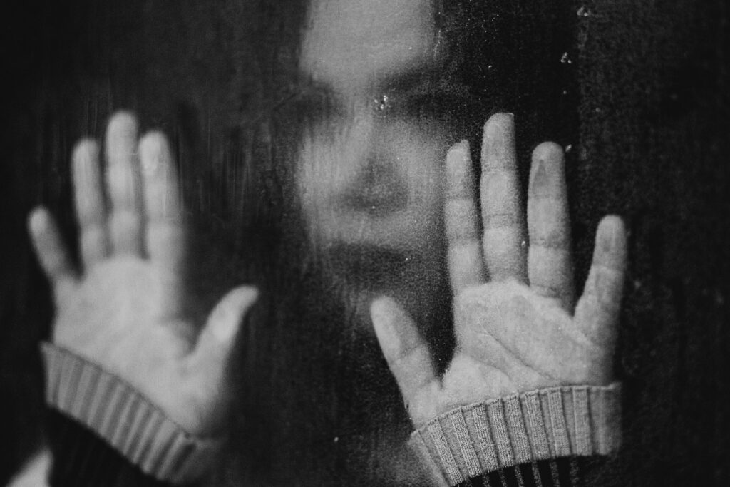 black and white photo of woman looking sad and holding out her hands in front of her face