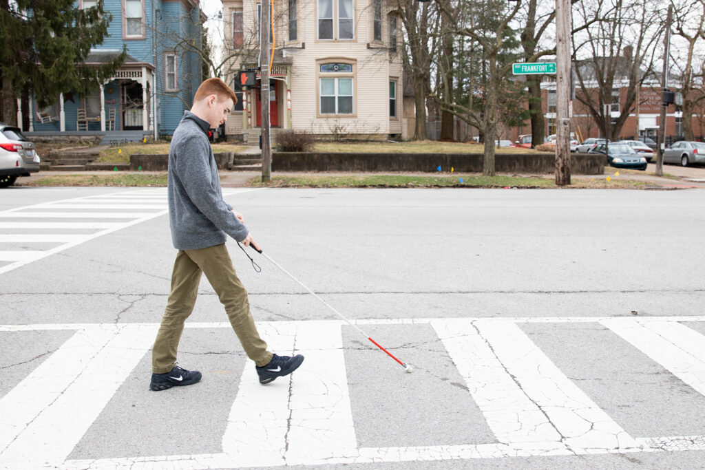 Young man walking on a pedestrian crossing using a white cane
