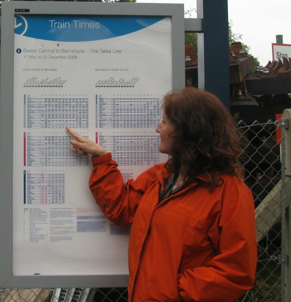 a person looking at a train schedule