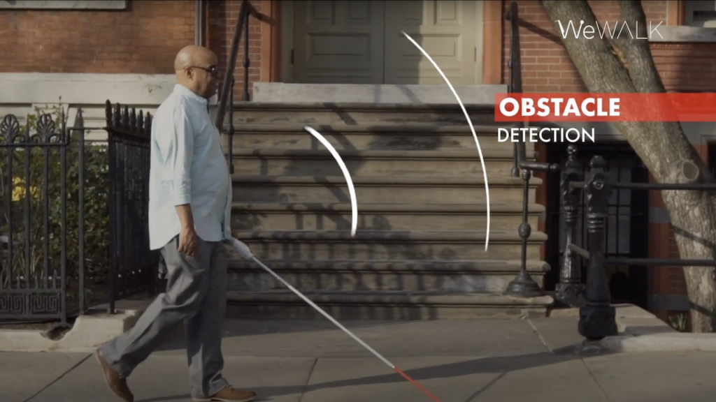 """person walking withi wewalk smart cane. picture indicates """"obstacle detection."""""""